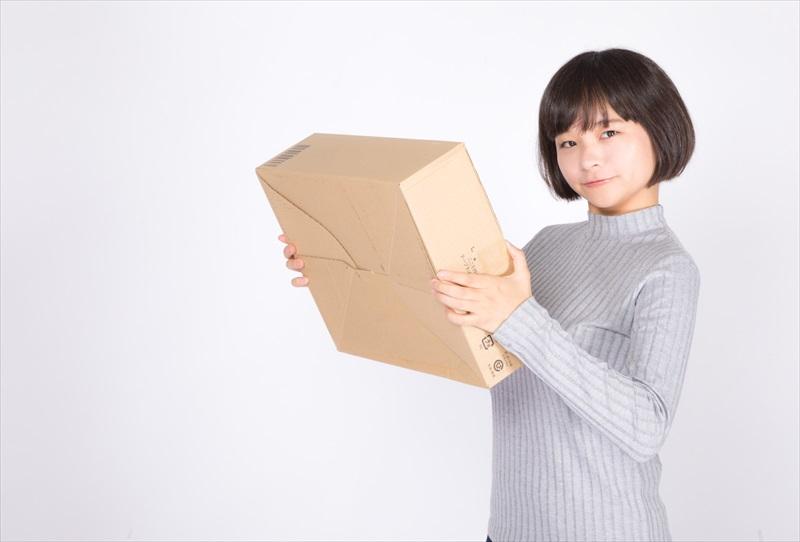 通販で購入した商品持つ女性